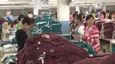sítí : Wide shot pan to garment workers iron completed garments in the ironing station at an Asian garment factory