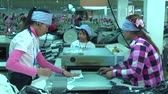sítí : Garment workers place fabric stripswith backing into a heat roller in a garment factory