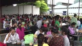 sítí : Garment factory workers eat lunch in mess hall, with exterior of factory bulding visible nearby