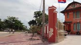 thai : Pan from unidentified cyclists to restored orange colored French colonial administration building in small town in Asia, with Cambodian flag flying nearby Stock Footage