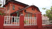 thai : Wide shot pan from street to side of restored orange colored French colonial building in Southeast Asia