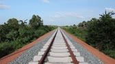 přepínač : Slight tilt up symmetrical wide shot perspective down newly laid railroad tracks in the Asian countryside