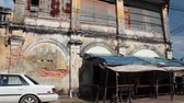 estragado : wide shot tilt down from second story of old French colonial building in Asia to street level view of broken brick wall with white car and old flapping tarp