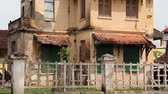 nowoczesne : Very dilapidated old French colonial building in Asia, with broken stucco and missing rooftiles; settle on aged concrete fence