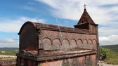 estragado : Side view of old abandoned French colonial church with crucifix in Southeast Asia, showing weathered brick and vegetation Vídeos