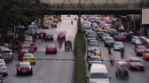 congestionamento : Time Lapse telephoto view of two lanes busy traffic in Asian city of Bangkok, Thailand, while pedestrians move through overhead footbridge