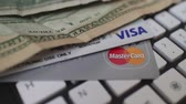 korumalı : Macro dolly reveal U.S. bills partially obscuring two credit  cards on a computer keyboard;     Trademarked logos are included as part of an editorially illustrative theme, suggesting concepts such as e-commerce and online purchasing.