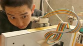 Reverse Close up of young Asian man watching the operation of a 3D printer as seen through the machine.  Camera moves to settle on printer tray close up.