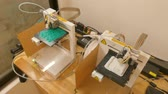 Overhead 2-shot of a pair of 3D printers  in operation in a maker-space coworking lab; one prints in green, the other in white. The camera lowers to settle on printer in foreground. One of a series by StockFootageWorld