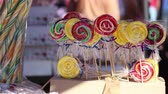 guloseima : Colorful lollipops, for sale, on the shelf at a fair. A lollipop is a type of confectionery consisting mainly of hardened, flavored sucrose with corn syrup mounted on a stick and intended for sucking or licking. Different informal terms are used in differ
