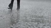 A black pants man steps through the hail storm. Sound included. Stock Footage