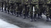 clothe : Close up shot of a platoon marching in cadency, wearing black army boots.
