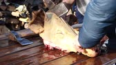 butchered : Butcher is slicing pigs head, for traditional meat specialties.