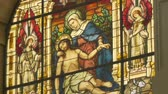 piety : Tilt shot of beautiful stained glass depicting Jesus and Saint Mary on the Descent from the Cross scene of Gospels.