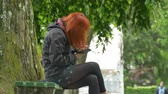 A redhead girl is using the smartphobe in the park sitting on a bench.