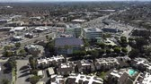 custo : Aerial, tracking, drone shot around a buildings rooftop, covered with Solar panels, on a sunny day, in Long Beach