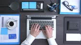Corporate businessman working at office desk, he is typing with a laptop, top view Vidéos Libres De Droits