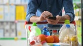 Man doing grocery shopping at the supermarket, he is leaning on a full shopping cart and using a smartphone Vidéos Libres De Droits