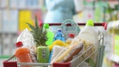Woman shopping at the supermarket and pushing a full cart, she is putting a bottle of milk in the shopping cart Vidéos Libres De Droits
