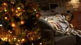 hora de dormir : Cute boy sleeping on sofa at home next to Christmas tree, he is waiting for Santa on Christmas eve: childhood and holidays concept