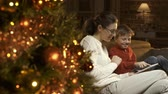tapping : Happy boy and mother using a digital tablet, Christmas tree with baubles in the foreground