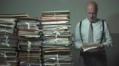 overloaded : Corporate businessman overloaded with paperwork, he is reading a file and browsing pages Stock Footage