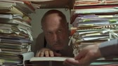 Office clerk working behind a wall of paperwork, he is peeking from a hole and taking a file, bureaucracy concept