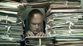 Busy office clerk working behind a wall of paperwork, bureaucracy and administrative process concept