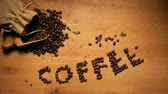 Fresh coffee beans spilling out of a sack onto a scoop with a the letters COFFEE on wooden background alongside.