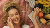 mobile phone : Beautiful vivacious blonde woman on a picnic lying on her back on a red and white checked rug chatting on a mobile phone Stock Footage