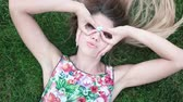 emberek : happy woman wearing sunglasses woman lying on green grass Stock mozgókép