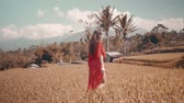 crochet : Beautiful young woman in red transparent dress walking along the rice field - video in slow motion