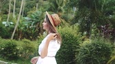 delighted : Fashion beauty portrait of smiling girl in white dress and straw hat walking in the tropical garden Stock Footage