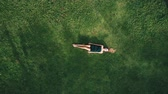 antena : Aerial top view of happy woman relaxing on the grass during sunny summer day