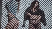 Two beautiful women in lingerie and jacket dancing with projected pattern on them. Music, nightclubs, shows and entertainment concept - video in slow motion Stock Footage