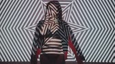Portrait of woman in lingerie and jacket posing with projected pattern on her. Music, nightclubs, shows and entertainment concept - video in slow motion