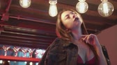 Portrait of sexy brunette woman in lingerie and jacket posing on the bar table in luxurious modern interior - video in slow motion
