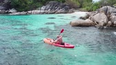 cieli : Aerial drone view of man kayaking in crystal clear lagoon sea water during summer day near Koh Kra island in Thailand. Travel tropical island holiday conceptAerial drone view of man kayaking in crystal clear lagoon sea water during summer day near Koh Kra