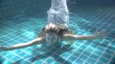подводный : Beautiful woman with long red hair swimming underwater in dress - video in slow motion