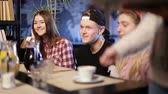 coffee cherry : Happy teenage friends sitting and chatting in cafe Stock Footage
