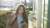 Smiling asian woman texting on smartphone outdoor Stock Footage