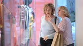 shopaholic : Excited women looking at clothes in store window Stock Footage