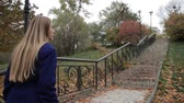 step : Stunning woman climbing staircase in autumn park
