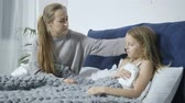 paper towel : Mother nursing her ill daughter in bed at home