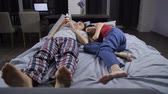 disinterest : Man busy with smartphone, wife sleeping in bed