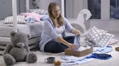 analık : Pregnant mom taking out baby clothes from gift box Stok Video