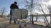 immigrant : Front view of homeless mature man pushing cart