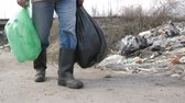 urban waste : Male legs walking at garbage dump with trash bags