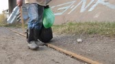 immigrant : Close-up male legs scavenging for plastic bottle