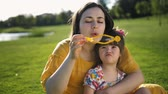 gastos : Mother blowing soap bubbles with special daughter